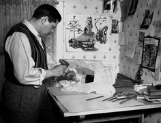 David Smith carving Sewing Machine, with Table Torso, on desk against wall, and Fascist Royalty, on the wall.