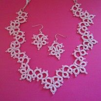 This soft pink necklace gently frames the neck with elegant swirls of loops and chains.