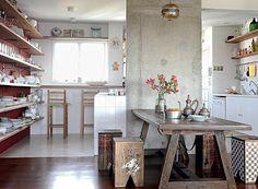 A estante, que começa na cozinha e termina na sala de jantar, guarda, além de louças e copos, livros e objetos de decoração. (Foto de Casa e Jardim)