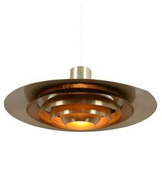 Mid-Century Modern Bronzetone Danish Pendant, c1967 | Rejuvenation - With its five tiers of reflector rings, lightweight aluminum design, and original Bronzetone lacquer, this spaceship-esque pendant is quintessentially Danish Modern. Made by Nordisk Solar Company and sold by Prescolite here in the U.S., it makes a design statement that has seen a steady ascent in recent years, as more and more people once again discover the charms of the populuxe era.