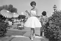 1962: This full skirt is enhanced by many starched petticoats, but in Palm Springs the sheer white cotton dress with spaghetti straps was a great way to stay cool. White kitten-heeled mules perfectly completed this bare resort look.