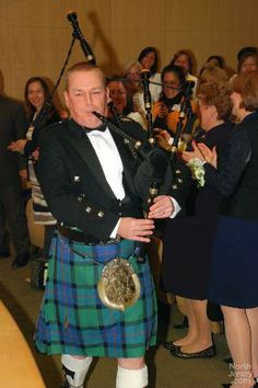 Christopher Robertson, RN, and manager of the Bolger Emergency Department at the hospital plays his bagpipe at the ceremony.