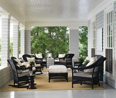 Wicker And Seagrass    Chic black wicker furniture with white cushions is arranged in two welcoming groupings on seagrass rugs on this large summer porch.