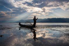 """Lago Inle, Birmania. Racconta l'autore: """"il sole sta per tramontare dietro le montagne creando una corona di raggi. Scatto alcune foto, ma manca qualcosa. La fortuna è dalla mia parte. Un pescatore si avvicina su una piccola canoa. Ora la foto è perfetta""""."""