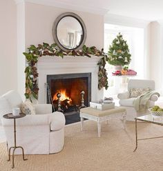 A silver grey textured geometric rug showcases the beauty of whites in the fireplace, in the Neoclassical ottoman and the upholstered chairs. A round mirror amplifies the shimmer from the silvery ornaments in the magnolia leaf and pine cone garland (next image). Traditional Home Magazine image