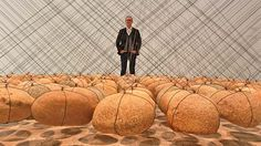 Dr Michael Brand, director of the Art Gallery of NSW pictured with Suspended stone circle 2 by Ken Unsworth.