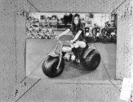 Model op driewielige motor, op de achtergrond kinderfietsjes en bromfietsen