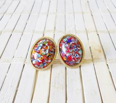 These striking clip earrings feature end of day glass cabochons which look like tiny millefiore pieces that are all mixed up and marvelous.  There are many vibrant colors in the glass, but predominantly they are tomato red.  The glass stones are framed with golden ropes.  These are not signed by a maker, but they mostly like were made in Italy.  Their condition is very good. No chips, dings, or dents, and no signs of wear to the gilded finish.  Great for adding a pop of color to your…