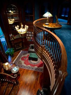 A Family Castle and Fantasy Indoor Pool  An inviting loft space bordered by a curved wood banister overlooks the home's opulent library. This room's wood paneling makes use of cherry and walnut stock harvested from the forest on the property.