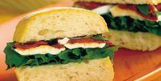 Sanduíche de tomate seco e rúcula  .1 pão ciabatta grande (300 g)   .1 xícara (chá) de folha de rúcula rasgada (40 g)   .1 bola de mussarela de leite de búfala (180 g), cortada em fatias finas   .1/2 xícara (chá) de tomate seco picado (100 g)   .10 folhas de manjericão rasgadas   .4 colheres (sopa) de azeitona preta picada   .4 colheres (sopa) de azeite de oliva   .1 pitada de sal   .1 colher (sopa) de vinagre