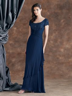 Crinkled silk chiffon dress with short sleeves, wide scoop neckline, hand beaded bodice with center front ruched midriff, mock wrap layered bias cut skirt. Matching shawl included. Sizes: 4 – 20