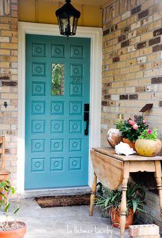 Turquoise front door with light brown brick