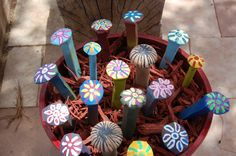 Image Only---Painted railroad spikes. What a clever way to add a pop of color to your garden and a good use for an old flowerpot that is just sitting around.