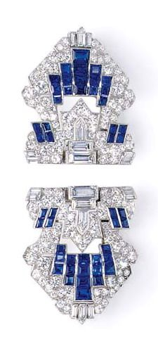 A PAIR OF ART DECO SAPPHIRE AND DIAMOND CLIP BROOCHES  Each openwork shield-shaped plaque set with circular and old European-cut diamonds, enhanced by a baguette-cut diamond and calibré-cut sapphire geometric pattern, mounted in platinum, circa 1925
