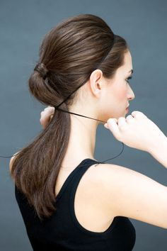 Secure hair into a ponytail and then place a string, ribbon, or, if you want to be a little edgier, a thin piece of leather close to your hairline and tie it at the nape of your neck, over the pony.