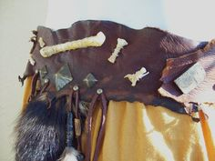 Unwrought Racoon Belt by ArchaicLeatherworks on Etsy, $145.00 -- Made from scraps of deerskin in varying shades of brown, this tattered belt is decorated with a multitude of trinkets including Turkish buttons, coins, antioqued animal bones, feathers, beads, giant 1 inch antique brass spots, and a raccoon tail. Fits best at a 32-40 inch measurement. Width of the belt is about 3 1/2 inches.