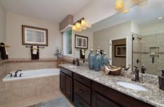 Master bathroom with granite countertops, dark wood cabinets and a jacuzzi bath tub.