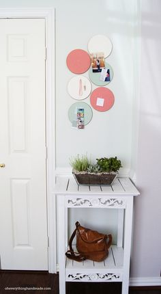 Ikea cork trivets painted with craft paint, or covered with fabric, as bulletin board. Hang with command strips.