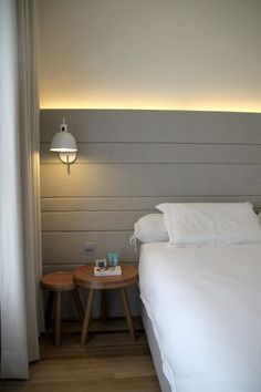 Lovely grey bed head and lighting matches perfectly with the pure white linen.