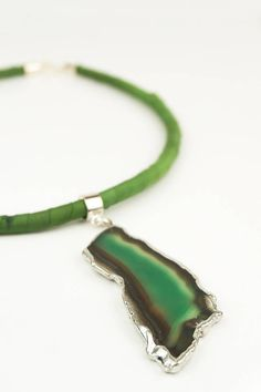 This green agate pendant on a silk wrapped cord necklace features a green agate slice with brown tones and silver plating. The pendant is strung on a silk-wrapped cord, easy on the skin in all seasons. An extremely stylish and unusual way to accessorise for work or play.  One-of-a-kind hand painted silk and pendant necklace Total length approx 45 cm (18 inches) Pendant size: 50 x 25 mm approximately 100% silk with agate slice gemstone pendant, leather cord filler and metal findings Care: do…