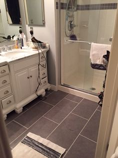 Gray plank tile floor. White shower tile and vanity with gray marble top. All from lowes