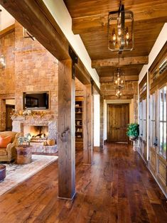 Love this fireplace, wood-beamed high ceilings and wood floors in this contemporary barn remake home