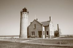 Lighthouse - Mackinac Point, Michigan. Bright sunny morning for Lake Huron light with white picket fence. Includes lighthouse tower and keeper's quarters. In sepia.