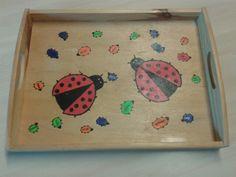 Dienblad met vingerafdrukken van de kinderen.  Hier zijn lieveheersbeestjes van gemaakt met zwarte stift.