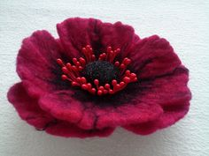 Red magenta poppy flower with black details. Handmade from 100% pure merino wool which is hand washed, brushed and colored.  On the back hair clip and brooch pin.  Dimension: 10 cm (3.9)  100% natural and eco friendly. All Made with Wet Felting process. It will cheer you up no matter how you wear it : pinned to your bag, coat, dress, hat or a scarf.  If you have any questions,please contact us! Handmade with love and care.