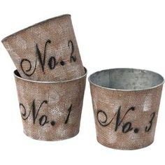 Set of three tin planters with numbered fabric coverings.       Product: 3 Piece planter set Construction Material: Tin and fabric Color: Tan and black Features: Elegant typography       Dimensions: 6.5 H x 7.25 Diameter each