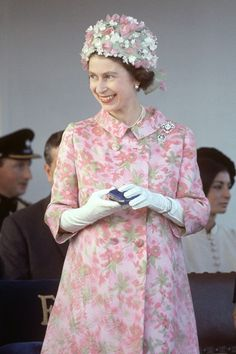 VogueUK:  1967 – Enjoying the fashions of the day, the Queen wore a pink and green patterned double-breasted coat by Hardy Amies and matching floral hat for a royal visit to Malta. She accessorised with white gloves, a pearl necklace and two diamond brooches.