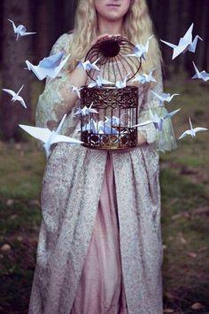 Girl holding birdcage with origami birds art