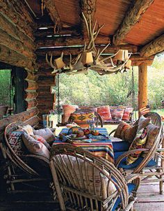 Rustic Porch.. antler chandelier... twig chairs... log cabin