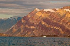 Greenland. 1,900m-high, stripy cliffs in Segelsällskarpet Fjord. The colourful layers are part of the Eleonore Bay group and are made up of alternating layers of limestones, dolomites, mud rocks and quartzites.