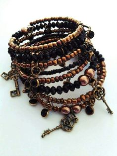 My favorite black bronze memory wire bracelet. I use material from the http://www.doreenbeads.com. This bracelet is made with bronze tones of seed beads (I adore them) also here are acrylic delicate charms that I only able find on doreenbeads.com and some key pendant pendants.