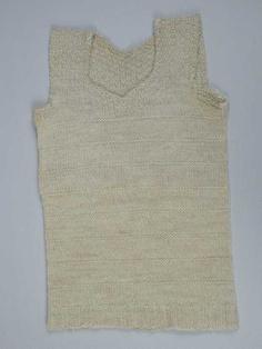 Kinderhemd of borstrok, gebreid van crèmekleurige wol in tricot- en reliëfsteken, blokjespatroon op schouders en langs de hals. En kriebelen .....