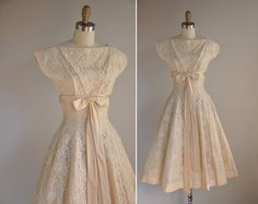 1950s dress with pale lace, bow at empire waist, fitted through the natural waist and flared at the bottom