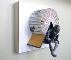 """Nice wall-mounted sculptures made from books by Tennessee via Malaysia artist Daniel Lai. The sculptures feature clay figures in """"Thinker"""" poses positioned amongst artfully folded leaves from various books. These capture the quiet, contemplative mind-space brought on by a"""