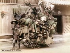1890's. This vendor doesn't only sell baskets and brooms (箒), but also brushes, sieves (笊), ladles (杓) and more, all piled up high on his cart, called a daihachiguruma (大八車). To protect himself from the elements, he is wearing a broad bamboo hat, known as a bachoukasa (バッチョウ笠). Vendors like him used special calls to make potential customers aware of their arrival.