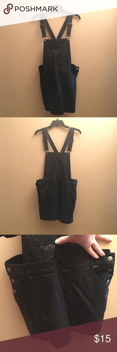 FOREVER 21 Black leather overall dress. Open back with cross cross buckles. Buttons on side for flexible fit. Sadly this was just a little too snug on my behind. Typically I wear an L, or Xl when it comes to rompers or items like this one because of  legs and bigger butt. May fit M or L. Perfect piece for summer or add a long sleeve and tights for transition to fall/winter! 100% polyester Forever 21 Dresses Backless