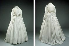 Day dress, ca. 1860s, in a white jaconet print with narrow lace trim. Two glass buttons in the front; loose belt with rosette, edged with lace. National Museum of Denmark