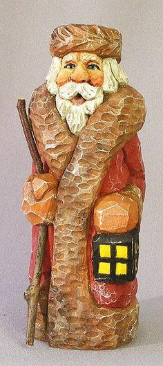 Santa woodcarving by Russell Scott - Santa is wearing a big coat and holding a lantern. SA152 8 X 3 X 3 Hand-crafted wood carving. This folk-art wood art will brighten any holiday decor or would be an excellent addition to a Santa collection. Many people report they display their Santa