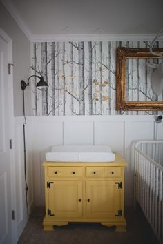 girl - woodland nursery - love the beadboard (?) w/ the half wall of wallpaper above it. perfect and not overwhelming.