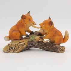 SOLD - Vintage pre-owned decorative collectible HOMCO fox figurine.  The bisque porcelain ceramic figurine features two baby red fox playing tug of war with a tree branch while perched on an old log.