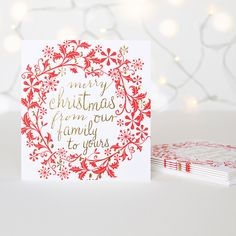 A simple matt white card featuring an embossed red wreath and luxurious gold 'merry Christmas from our family to yours' lettering. Caroline Gardner charity Christmas card packs are a great way to help support Meningitis Now