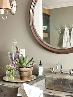 A polished chrome faucet lives with a bronzed mirror frame and a chipped-paint wall sconce.