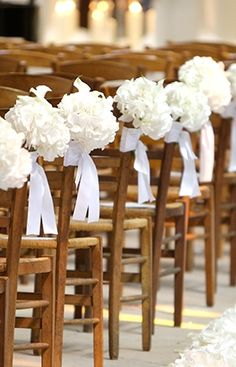"""White hydrangea """"bouquets"""" wrapped in white ribbon are tied to each chair along the aisle at this wedding decorated by Jeff Leatham."""