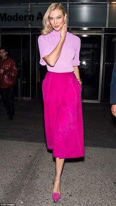 Model behavior! Kloss radiated retro elegance in a tight orchid-colored sweater and suede ...