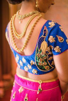 Indian Wedding Jewelry - Layered Three Gold Necklaces | WedMeGood | Blue Indigo Blouse with Peacock Caricatures, Pink Lehenga #wedmegood #indianwedding #indianbride #jewelry #indianjewelry #gold #necklaces #blue #peacock #choli