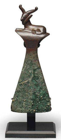 A BACTRIAN COPPER AXE HEAD   CIRCA LATE 3RD-EARLY 2ND MILLENNIUM B.C.   With a flaring flat-edged blade, the shaft surmounted by a reclining goat with raised horns curving at their tips, a thick beard and elongated muzzle, the eyes and facial features delineated, a zigzag band in contrasting color cascading along the shaft  6¼ in. (15.6 cm.) high
